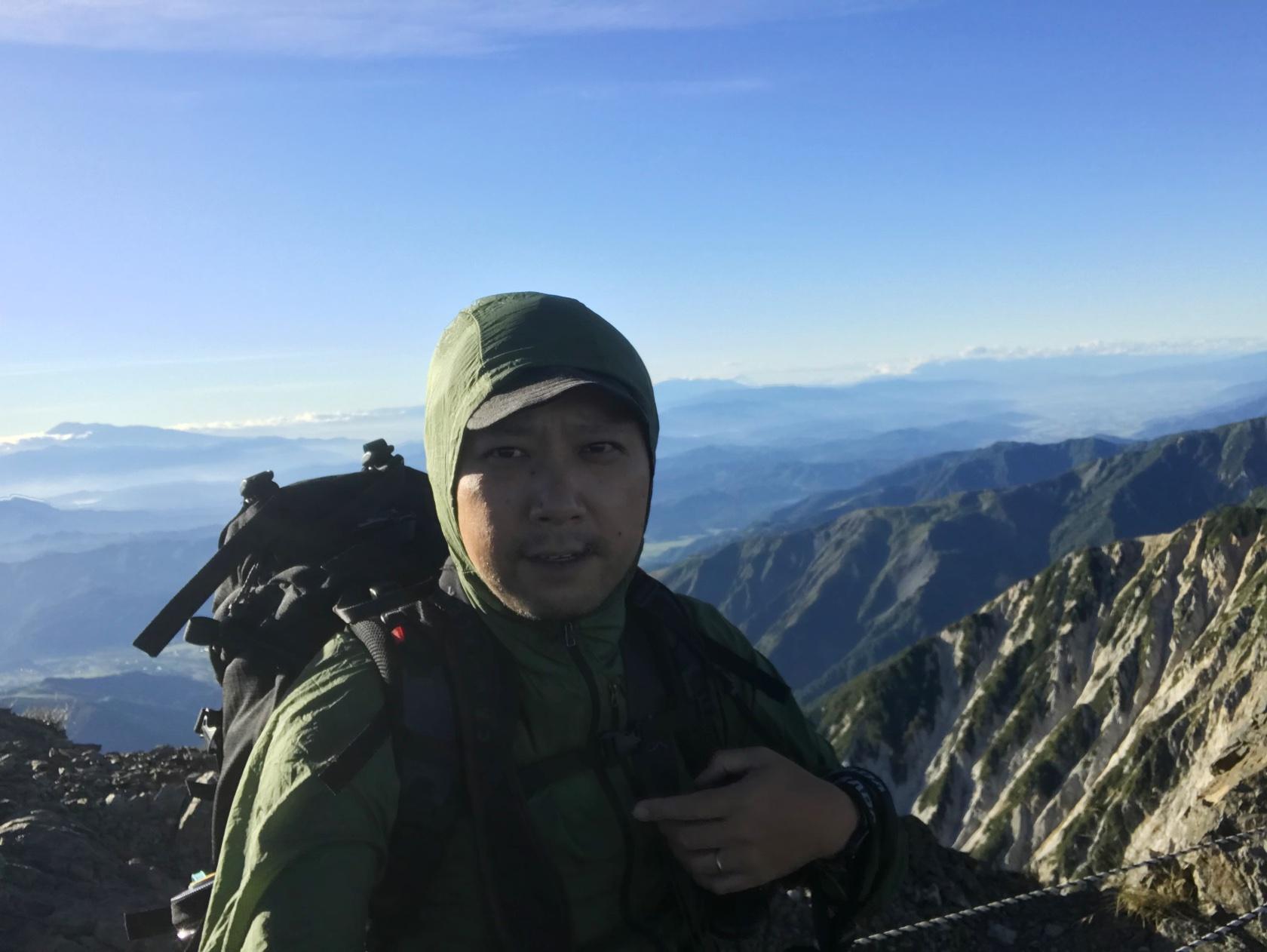 夏の北アルプスの稜線で爆風に吹かれている著者。 Patagonia のフーディニジャケット(通称「パタゴニアのシャカシャカ」)で風を凌いでいる。